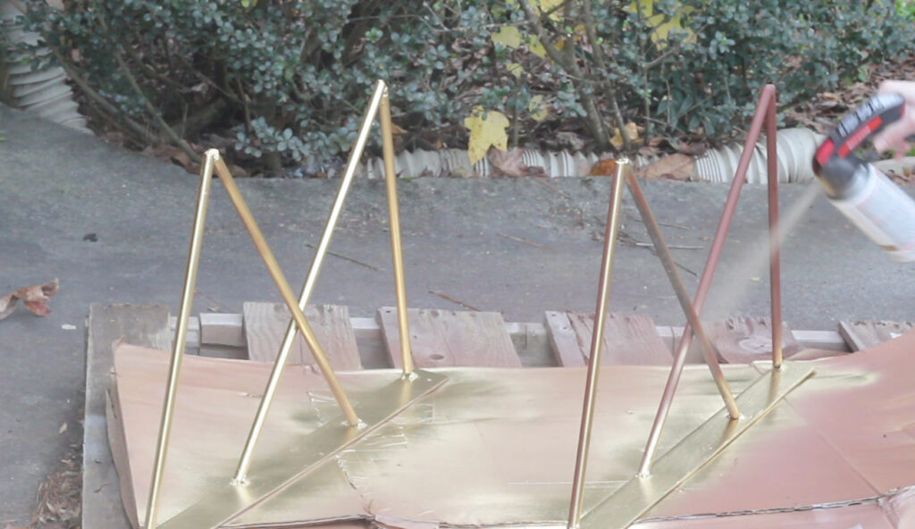 Spray painting steel table base with gold metallic spray paint.