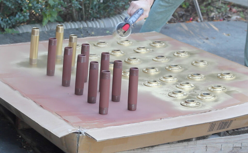 Spray painting pipe and flanges with gold spray paint.