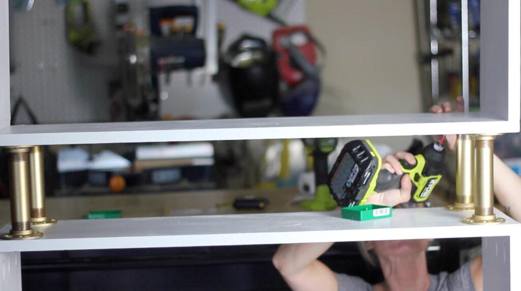 Assembling a DIY pipe bookshelf.