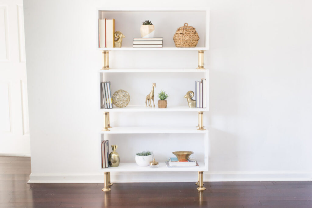 "Learn how to build a DIY pipe bookshelf! This one puts a modern ""glam"" spin on this typically industrial style project."