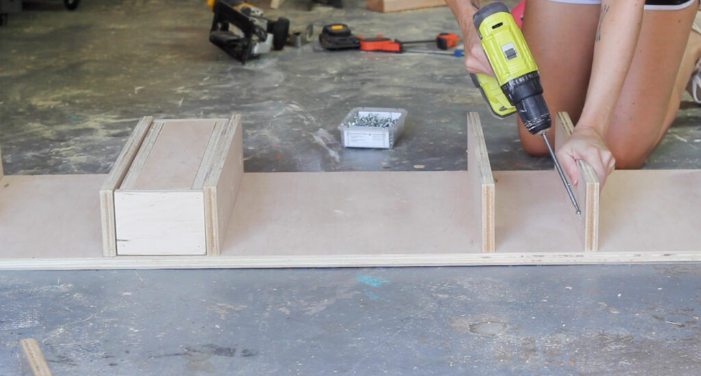 "Learn how to make this DIY plywood desk with hairpin legs and ""secret"" storage bins that pop out using magnets! This step by step tutorial will show you how."
