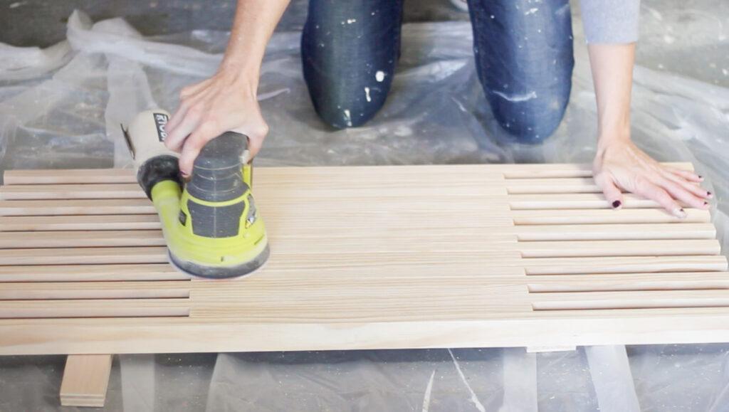 Sanding DIY tabletop with a RYOBI sander.