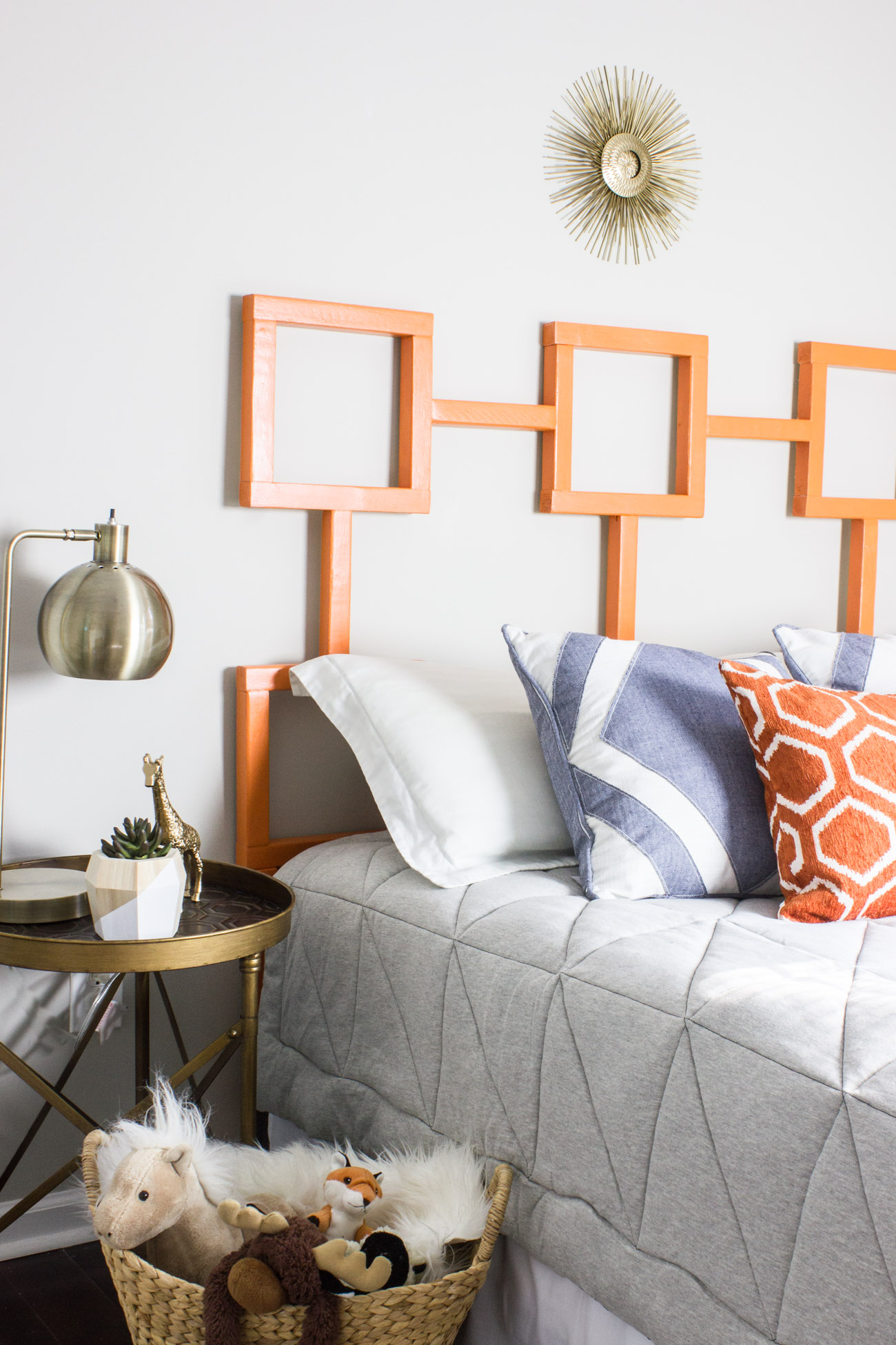 Learn how to make this DIY headboard with a fun geometric shape! This one is a yummy orange but you could customize it with any finish or color you like.