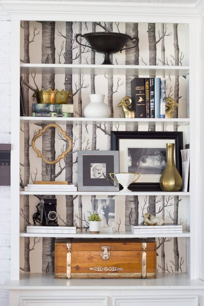 "These built-in bookshelves are backed with ""Woods"" wallpaper from Anthropologie, and contain a mix of old and new decor, including an antique wooden box which is a family heirloom."
