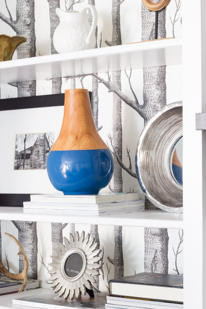 Loving these styled shelves! The wallpaper backing and that pop of blue on the vase are perfection.