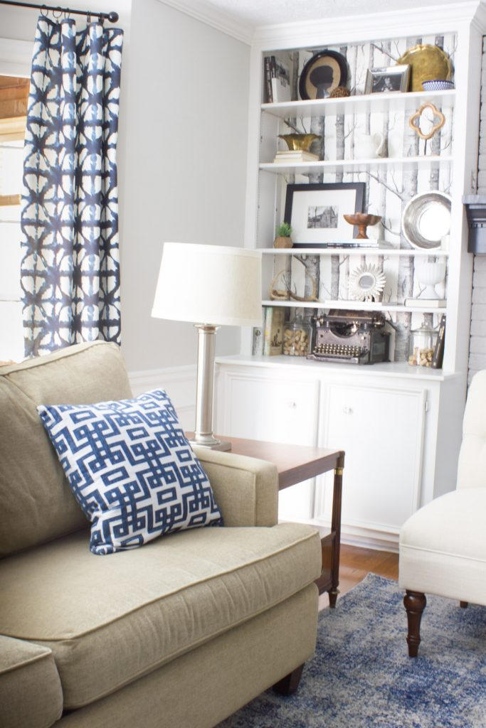 In love with this family room makeover in shades of blue and indigo! This Faded Shadow Mystique Rug from Rugs USA anchors the room, and Shibori patterned curtains, mixed patterns, Minted art, and more, all add to the beauty of the space!