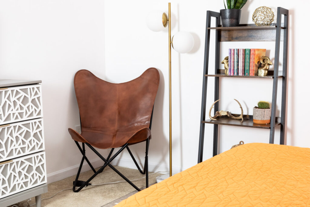 Leather butterfly chair, modern floor lamp, and bookshelf in a teen room.