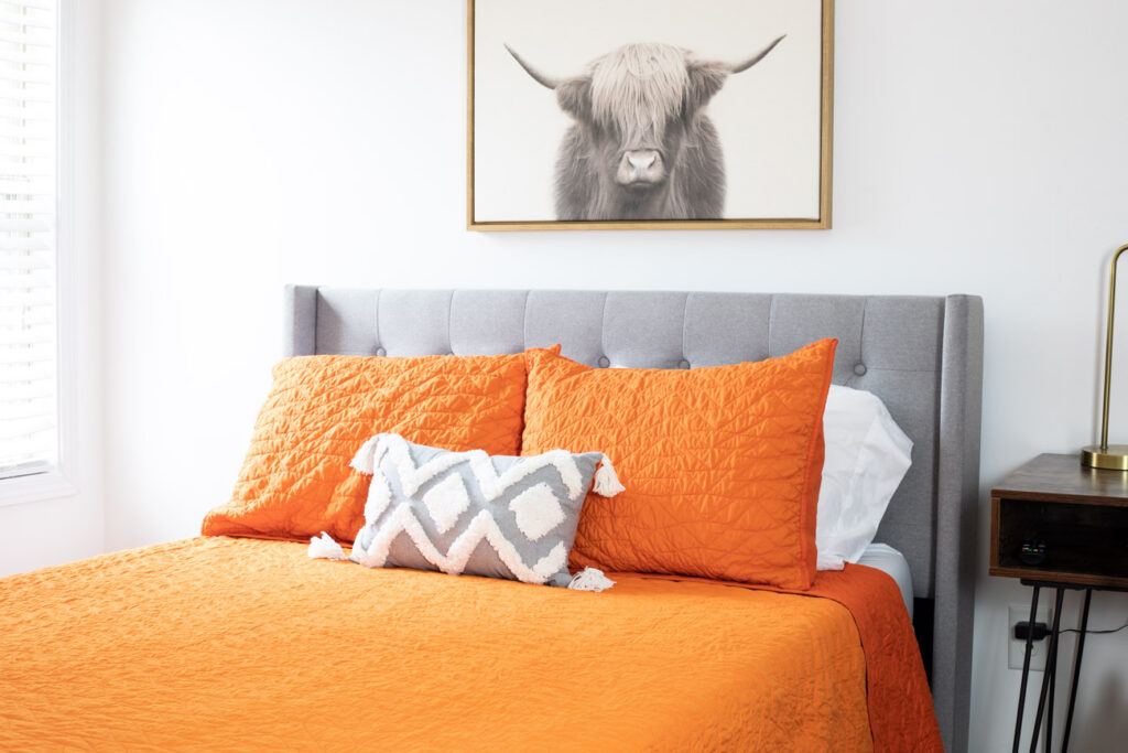 Orange and gray bedroom with highland cow art.