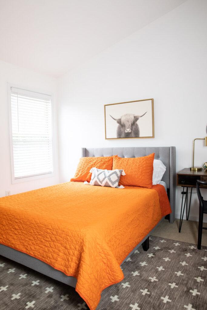 Orange bedding, gray headboard, highland cow art in teen bedroom.