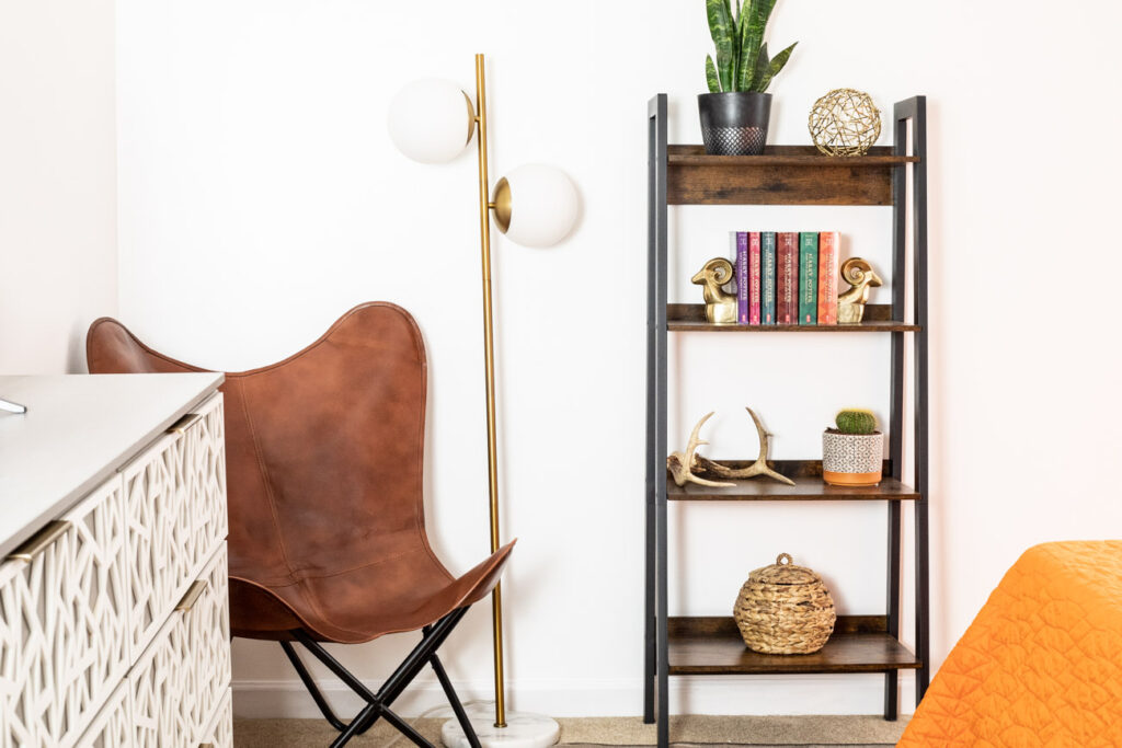 Leather butterfly chair, modern floor lamp, and bookshelf in a teen bedroom.