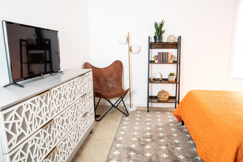 Leather butterfly chair, modern floor lamp, bookshelf in teen bedroom.