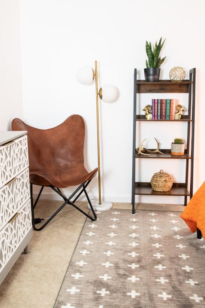 Leather butterfly chair, modern floor lamp, bookshelf in teen room.