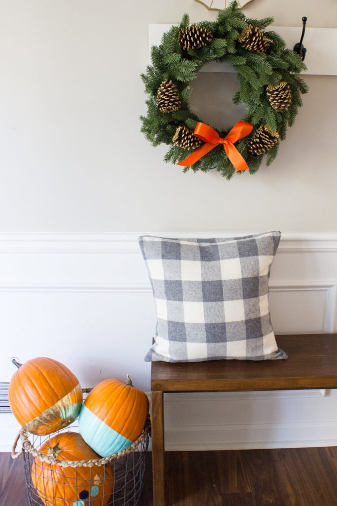 I'm loving this fall entryway decorated with painted pumpkins and a beautiful Kennedy Fir Wreath from Tree Classics!